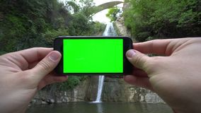 Hands Holding a Phone with a Green Screen. Hands holding using a smapthone with a green screen oute. Taking pictures of the waterfall. Close-up shot Stock Photography