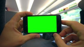 Hands Holding a Phone with a Green Screen on the Train. Tbilisi, Georgia - 15 September 2017: Hands holding using a smapthone with a green screen on the train Stock Images