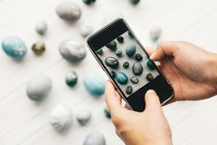 Hands holding phone and taking photo of stylish easter eggs on rustic white wooden background. Modern easter eggs painted with. Natural dye in grey marble color stock photography