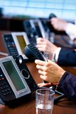 Hands holding phones. Close-up of hands holding landline phone recievers at customer service office Royalty Free Stock Images