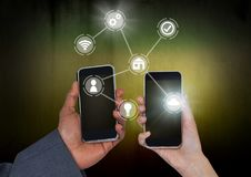 Hands holding phones with icons interface of internet of things. Digital composite of Hands holding phones with icons interface of internet of things Royalty Free Stock Photos