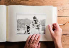 Hands holding photo album with picture of senior couple. Studio Stock Photography