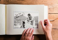 Hands holding photo album with picture of senior couple. Studio Royalty Free Stock Images