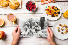 Hands holding picture of senior couple, breakfest meal. Studio s Stock Photo