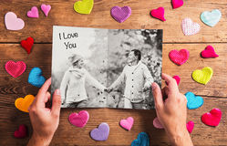 Hands holding picture of senior couple, colorful hearts. Studio Royalty Free Stock Photo