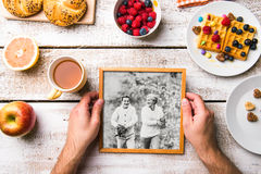 Hands holding picture of seniors, breakfest meal. Studio shot. Royalty Free Stock Images