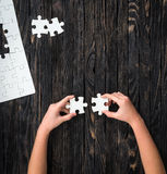 Hands holding pieces of white puzzle on dark table Stock Photo