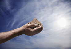 Hands holding a pile of soil with sun and sky in the background Stock Photography