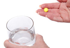 Hands holding a pill and a glass of water Royalty Free Stock Photos