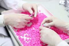 Hands Holding Pills - Quality Control Stock Photography