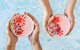 Hands Holding Pink Berry Yogurt Smoothie Bowls. Two pairs of hands, one male and one female, holding two different pink berry smoothie bowls. The smoothies are Stock Photography