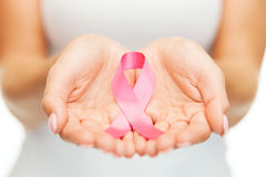 Hands holding pink breast cancer awareness ribbon. Healthcare and medicine concept - womans hands holding pink breast cancer awareness ribbon Stock Photography