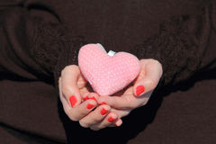Hands holding a pink heart stock photo