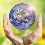 Hands holding the planet on blurred green bokeh background color of a natural tree with leaves, facing the sun-flared. The preservation of peace bio, CSR Stock Images