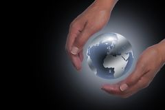 Hands holding planet earth. In black background stock image