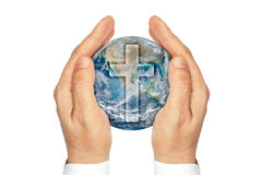 Hands holding the planet Earth with the Christian cross . Stock Photos