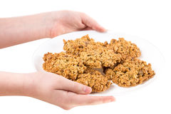 Hands holding plate with oatmeal biscuits. Royalty Free Stock Image