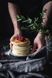 Hands holding plate with stack of pancakes. Stack of pancakes. Man hands serving pancakes with raspberries. Beautiful food still life. Natural light, slightly Royalty Free Stock Photography