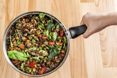 Hands holding a pot with a quinoa stew royalty free stock photography