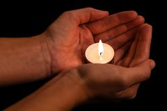 Hands holding and protecting lit or burning candle candlelight on darkness. Black background. Concept for prayer, praying, hope, vigil, night watch Stock Image