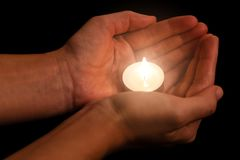 Hands holding and protecting lit or burning candle candlelight on darkness. Black background. Concept for prayer, praying, hope, vigil, night watch Royalty Free Stock Photography