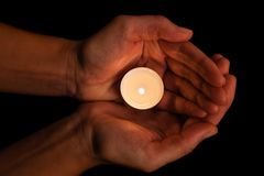 Hands holding and protecting lit or burning candle candlelight on darkness. Black background. Concept for prayer, praying, hope, vigil, night watch Royalty Free Stock Images