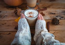 Hands holding pumpkin spice latte in glass cup, on wooden background royalty free stock image