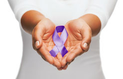 Hands holding purple awareness ribbon. Healthcare and social problem concept - womans hands holding purple domestic violence awareness ribbon royalty free stock photo