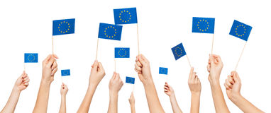Hands holding and raising European Union flags Royalty Free Stock Photo
