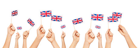Hands holding and raising flags of Great Britain Stock Photos