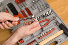 Hands holding ratchet and head over toolbox Stock Images