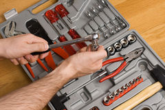 Hands holding ratchet and head over toolbox Royalty Free Stock Images