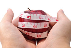 Hands holding a red apple with measuring tape Stock Photos
