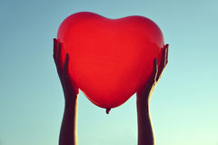 Hands holding red balloon in the shape of heart Stock Photography