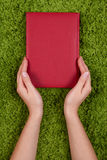 Hands holding red book stock images