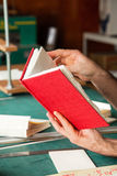 Hands Holding Red Cover Book At Table Stock Photo