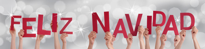 Hands Holding Red Feliz Navidad. Many Hands Holding the Red Spanish Letters Feliz Navidad Which Means Merry Christmas on a Festive Background stock photos