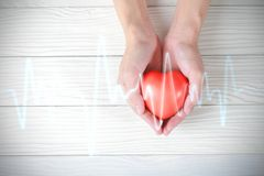 Hands holding red heart with pulse. medical concept.  royalty free stock image