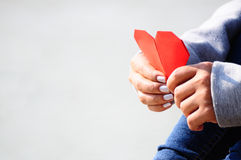 Hands Holding a Red Heart Shape Paper.  stock photo