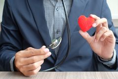 Hands holding Red heart and stethoscope stock image