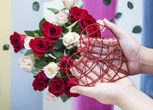 Hands holding red metal heart with roses background Royalty Free Stock Photos