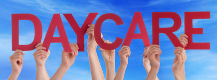 Hands Holding Red Straight Word Daycare Blue Sky royalty free stock photography