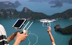 Hands holding a remote control drone camera while flying in the stock image