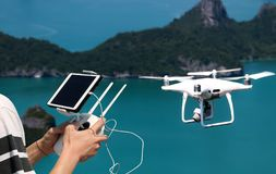 Hands holding a remote control drone camera while flying in the stock photo