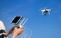 Hands holding a remote control drone camera while flying in the stock photography