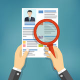 Hands holding a resume and a magnifying glass. Stock Images
