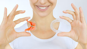 Hands holding retainer for teeth and tooth tray. Beautiful smiling girl holding retainer for teeth (dental braces) and individual tooth tray royalty free stock photo