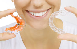 Hands holding retainer for teeth and tooth tray. Beautiful smiling girl holding retainer for teeth (dental braces) and individual tooth tray royalty free stock photography