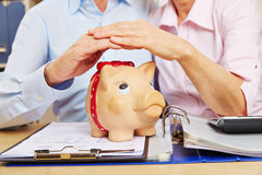 Hands holding roof over piggy bank Royalty Free Stock Photos