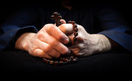 Praying Hands. Hands holding rosary beads and cross while praying Stock Image
